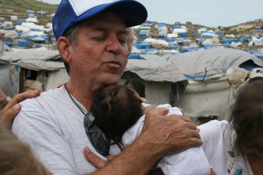 John A. Torres/FLORIDA TODAY Joe Hurston holds a sick child in a tent city in Haiti that began  after the 2010 earthquake. The photo was taken six months after the earthquake. A July 2010 photo of missionary Joe Hurston in Haiti. Photo by John A. Torres, FLORIDA TODAY.  Pubdate: 20100713 Publication:  Source: Florida Today Credit: John A. Torres Filename: Haiti july 2010 237.jpg  Photos from Haiti, by John A. Torres