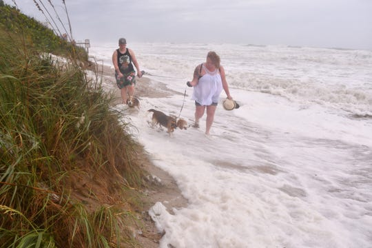 The Satellite Beach area at high tide Tuesday was suffered heavy damage from erosion. Just because there was no beach didn't stop these folks from taking their dogs to Canova Beach Dog Beach.