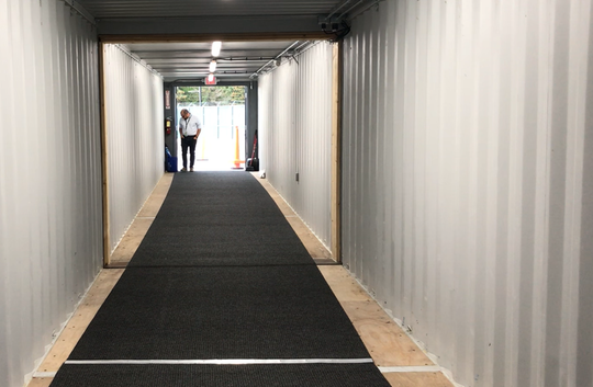 Nicolas Longo, deputy director of aviation at Burlington International Airport, inspects a new jetway under construction on Aug. 30, 2019. Metal shipping containers form the outer shell of the jetway.