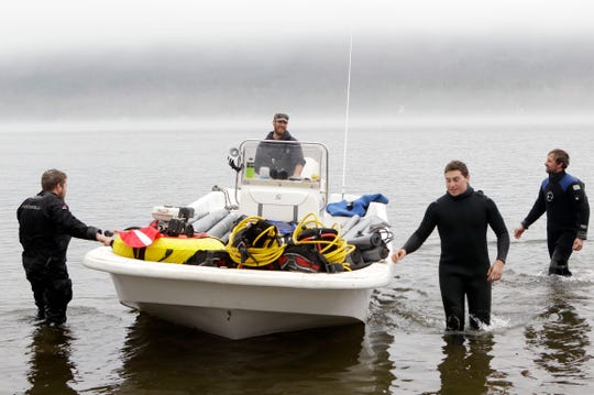 Workers launch a boat with materials to cover the floor of Lake George in Lake George, N.Y., on Tuesday, April 26, 2011.  Scientists and a corps of volunteers are launching an all-out assault on the tiny, invasive Asian clam that has clouded the azure bays of Lake Tahoe, in hopes of preventing it from befouling the crystal-clear waters of this beloved Adirondack lake.