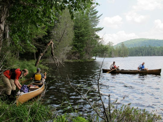 In this July 8, 2014 file photo, canoeists head out onto Third Lake in the Essex Chain Lakes tract near Newcomb, N.Y.  With his frequent trips to fish, boat and snowmobile in the Adirondacks, Gov. Andrew Cuomo has earned admiration from local leaders for his understanding of issues faced by the region's economically stressed hamlets. But some environmental advocates say his administration has placed local desires for easy recreational access ahead of wilderness protection, citing decisions favoring motor vehicles, bicycles and snowmobiles in recent additions to the 2.6 million acres of state-owned Forest Preserve.