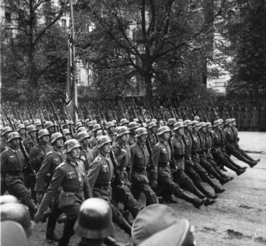 Nazi soldiers march through Warsaw.