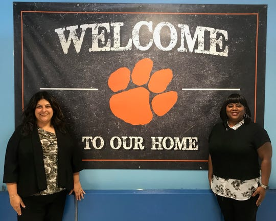 Soehl Middle School Principal Isabella Scocozza (left) and Vice Principal Gwendolyn Long in front of a new banner that will greet students and visitors in the Linden school's lobby.