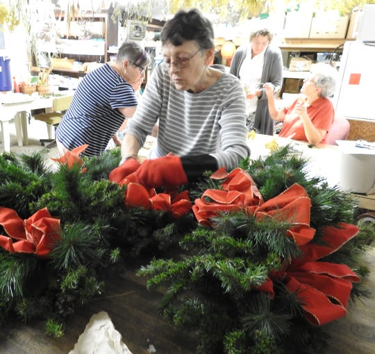 Jackie Fritz checks a lamppost swag with red ribbons from last year for reuse in Roscoe Village for the upcoming Christmas season.
