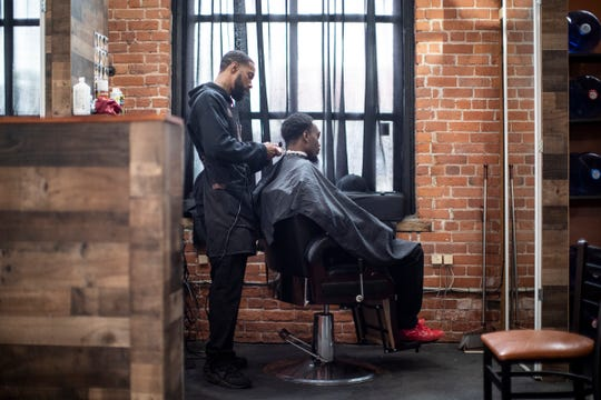 Paul Olden practices his barber skills on co-worker Haywood Edmunds at Evolutions Barber and Beauty in Detroit on Tuesday, Aug. 27, 2019.