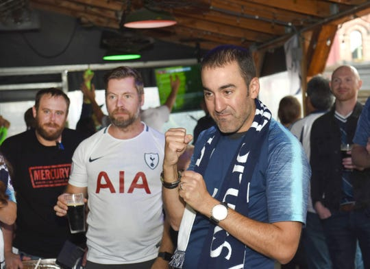 Charlie Rinehart (right), of the Detroit Tottenham supporters club, uses some body english to cheer Premier League team Tottenham during a watch party held at the Mercury Bar in Detroit during a match between Arsenal and Tottenham on Sunday, September 1, 2019.
