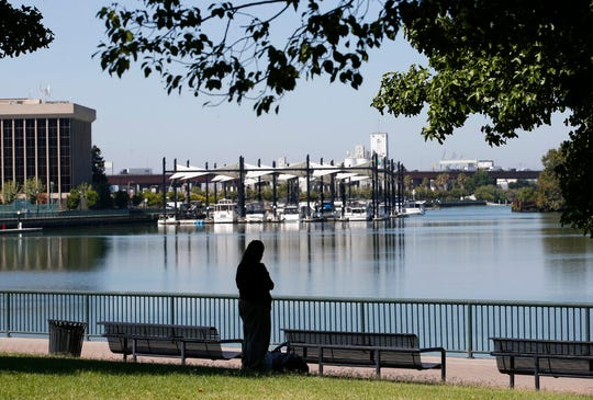 In this photo taken Wednesday, Aug. 14, 2019, a visitor takes in the view of the waterfront in Stockton, Calif. The area as been targeted for redevelopment as Stockton continues to reverse from the Great Recession when it known as the foreclosure capital of the country and for one of the nation's largest municipal bankruptcies. Now, it's led by Mayor Michael Tubbs who has initiated a program to give 125 people who earn at or below the median household income of $46,033 receive a $500 debit card each month to spend any what they want. Tubbs says the program, which is privately funded, could be a solution to the city's poverty problem.