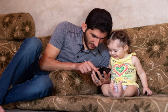 "In this Sunday September 1, 2019 photo, Syrian Abdel Hamid al-Yousef, plays with his 11-month-old daughter Aya, at a displaced settlement near the Turkish border called ""Mokhayyam al-Karamah,"" Arabic for ""Dignity Camp,"" near the town of Atmeh, in northern Syria. Al-Yousef lost his baby twins, his wife and 16 other relatives in the poison gas attack that hit Syria's Khan Sheikhoun in April 2017."