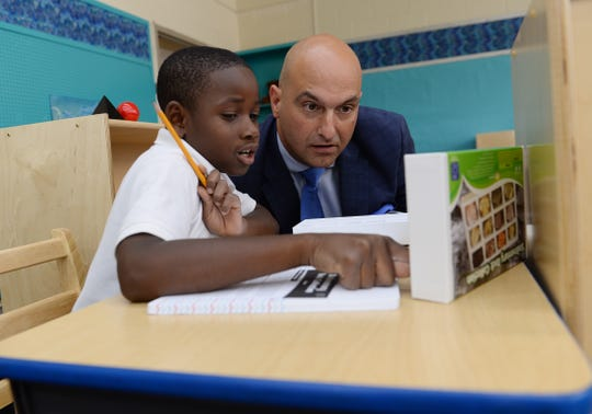 Dr. Nikolai Vitti, right, listen to Micah Broughton, 7, as he talks about his sedimentary rock collection during the first day of classes at Edmonson elementary school.  Dr. Nikolai Vitti, Superintendent of Detroit Public Schools visits the students at Edmonson Elementary school on September 3, 2019, Detroit, Mi.