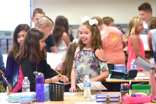 Friends Elizabeth Billeci, second from left, and Francesca Evola, center, both 9 and from Macomb, talk as students get to know each other on the first day of school at Duncan Elementary School on Tuesday.