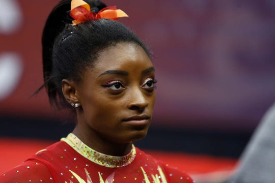 In this July 28, 2018, file photo, Olympic champion Simone Biles talks with her coach before the start of the U.S. Classic gymnastics competition in Columbus, Ohio.