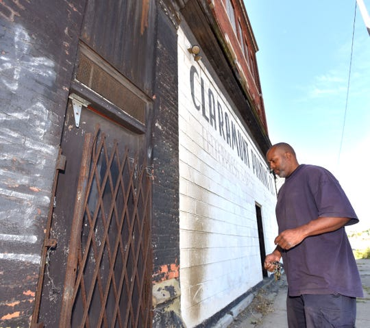 Property manager Raymond Fletcher of Detroit unlocks the door to the upper floors at the former Claramunt Printing Co. building.
