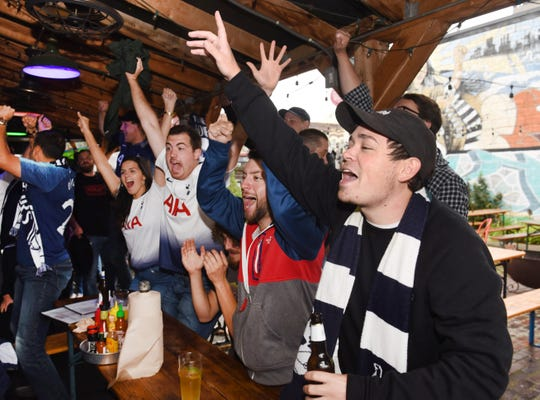 Tottenham soccer fans (from left) Sarah Johnson, Casey Copp, Correy Sarver, Antonio Munaco, and Brennan Richtes, of the Detroit Tottenham supporters club, cheer their Premier League team Tottenham score a goal during a watch party held at the Mercury Bar in Detroit on Sunday, September 1, 2019.