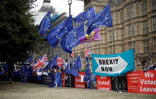 Leave and remain supporters wave flags and banners as they protest opposite Parliament Square in London, Tuesday, Sept. 3, 2019.