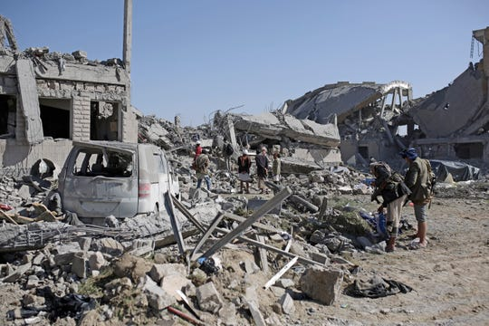 People inspect the rubble at a Houthi detention center destroyed by Saudi-led airstrikes, that killed at least 60 people and wounding several dozen according to officials and the rebels' health ministry, in Dhamar province, southwestern Yemen, Sunday, Sept. 1, 2019.