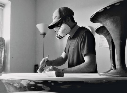Samuel Pawlak works on a prototype of his high-end coffee table Pangaea in his design studio.