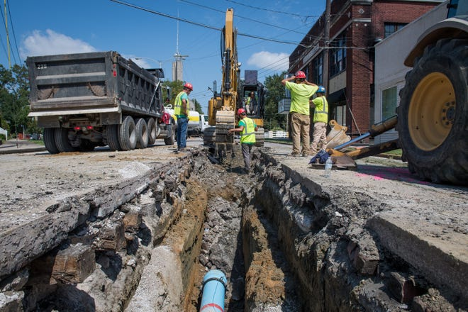 Workers with Deig Bros. Construction dig a trench down the center of Parrett Street, alongside of an old set of buried railroad tracks, as they install a new waterline near the Haynie's Corner Arts District Tuesday, September 3, 2019.
