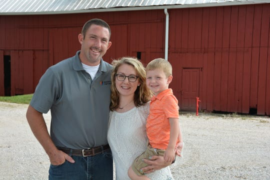 Eric and Megan Scheller and their son at their Evansville farm.