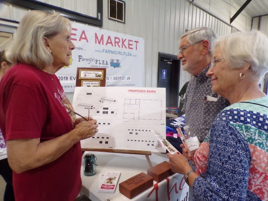 Marge Malone, a member of The Farm's board, talks to Jerry and Jan Warstler of Sturgis, MI about the future projects including a barn with animals.