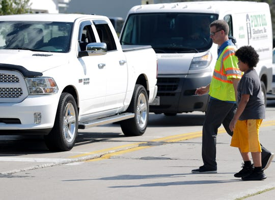 """Brown County Principal Planner Cole Runge helps an Edison Middle School student cross the street Tuesday during Operation Frogger, which is designed to help educate drivers on yielding to pedestrians in order to make sure children are safe on their first day of school in Green Bay. """"He told me that he just didn't know when he should cross the street,"""" Runge said."""