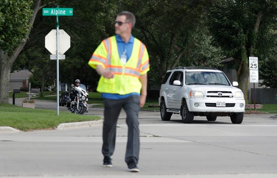 A Green Bay police officer, left, observes Brown County Principal Planner Cole Runge walk across the street to see if motorists will yield to him on Tuesday at Edison Middle School in Green Bay. Local law enforcement and municipal leaders hosted their Regional Crosswalk Education and Enforcement event known as Operation Frogger. This event is designed to help educate drivers on yielding to pedestrians in order to make sure children are safe on their first day of school.