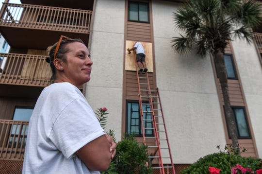 Kim Ryda, a manager at Anchorage Rentals along North Myrtle Beach, watches her father George Longazel cover up windows with plywood at the Anchorage Rentals in Myrtle Beach, South Carolina Monday, September 2, 2019. Many are preparing for Hurricane Dorian to arrive Wednesday evening.