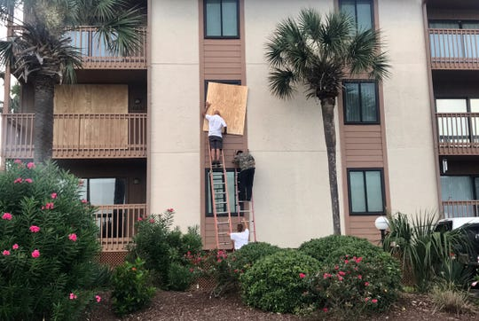 Kim Ryba helps Carlos Lopez and her father George Logazel board up windows at Anchorage Rentals in Myrtle Beach Monday.