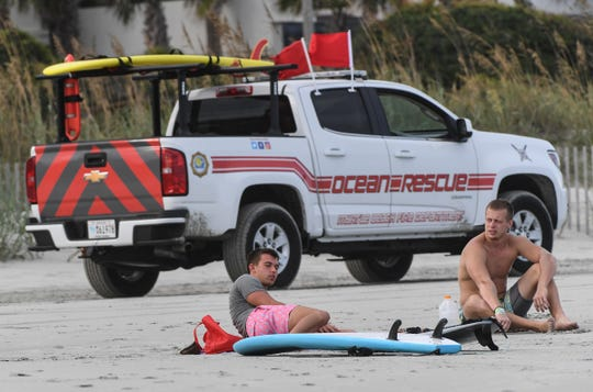 Tyler Gornak, left, and Sage Donaldson, right, both Coastal Carolina University students rest from surfing while the Ocean Rescue Myrtle Beach Fire Department ride by them with red flags at Myrtle Beach Monday, September 2, 2019. Many are preparing for Hurricane Dorian to arrive Wednesday evening.