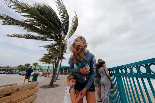 Kristen Davis watches the high surf from a boardwalk overlooking the Atlantic Ocean on Monday with her daughter Addie Davis 4, as winds from Hurricane Dorian blow the fronds of a palm tree palm tree, in Vero Beach, Fla.