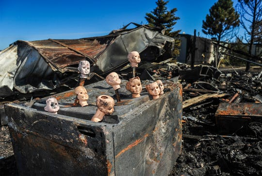 Porcelain doll heads sit on a charred dryer at the McIlwain family residence at 67 Golden Valley Loop, Tuesday.  The doll collection, which was destroyed in the Monday afternoon fire on the northwest side of Great Falls, was pulled from the rubble of a garage by firefighters.
