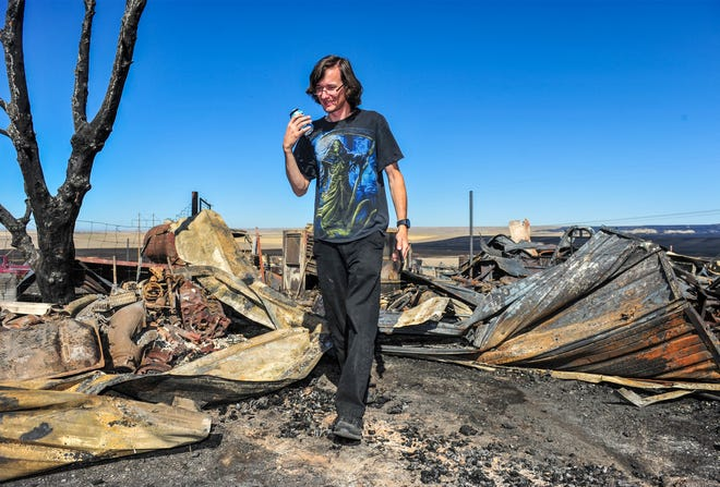 Jonathon McIlwain who lives at 67 Golden Valley Loop walks through the charred remains of an out building destroyed in Monday's fire northwest of Great Falls.