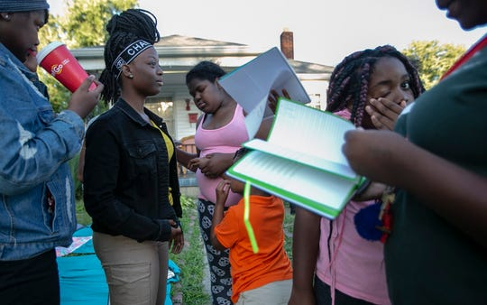 Cousins and family members gather in the front yard to read letters, Indianapolis, Wednesday, Aug. 28, 2019. Nicholas Nelson, 16, and his sister Ashlynn Nelson, 15, were fatally shot on the morning of Aug. 23, at their family's apartment in Indianapolis, and these letters are well wishes from loved ones.