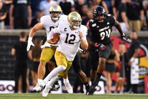 Notre Dame Fighting Irish quarterback Ian Book (12) runs the ball in the first quarter against the Louisville Cardinals at Cardinal Stadium.