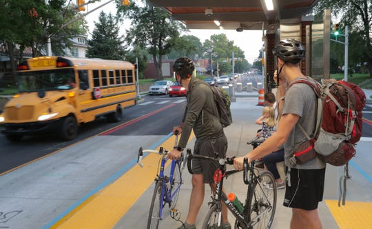 Bicycle commuters wait for a Red Line bus on Tuesday, Sept. 3, 2019.