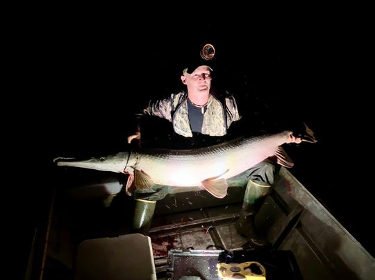 Brad Baugh of Cleveland holds a 6-foot, 2-inch alligator gar that was snagged while casting at a submerged alligator.