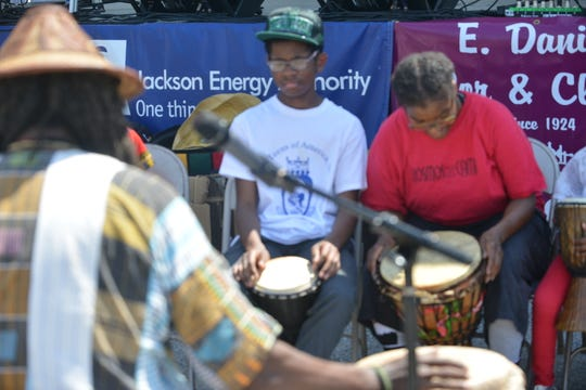 Dante Yarbrough listens as Baba Musa Amen teaches him and others about African drums, what they're made of and how to play them at the 2019 African Street Festival in Jackson.