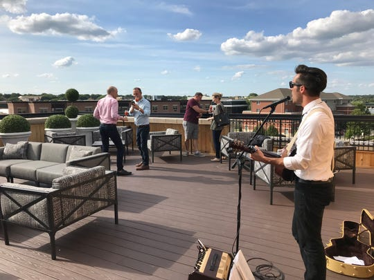 Musician Josh Calhoun entertains guests gathered for a party on the roof of the Hotel Goodwin in downtown Beloit, Wis.