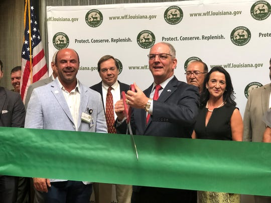 Gov. John Bel Edwards cuts the ribbon at a ceremony celebrating the new Louisiana Department of Wildlife and Fisheries regional building.