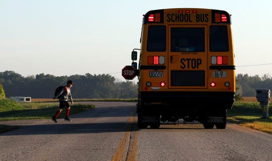 A student cross Carroll Southern Road Tuesday morning, Sept. 3, 2019, in Greenfield Township to board a Lancaster City Schools bus.