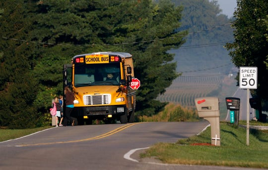 Students are led across Lithopolis Road Tuesday morning, Sept. 3, 2019, to board a Lancaster City Schools bus in Greenfield Township.