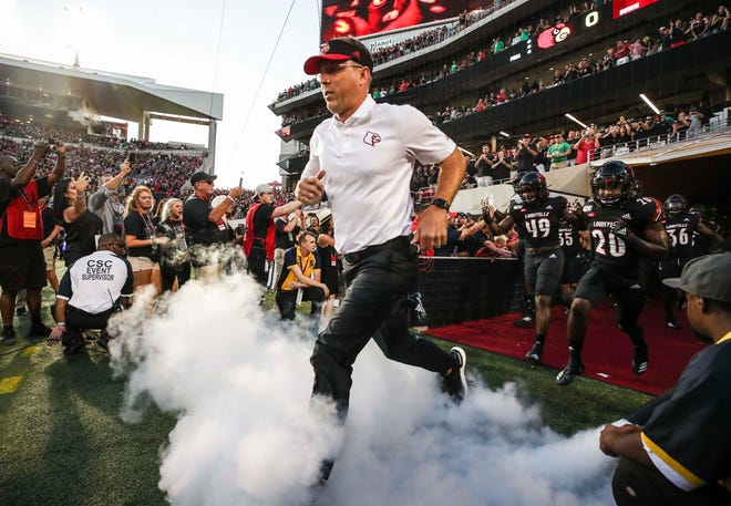 Louisville head coach Scott Satterfield runs out of the tunnel for his first game as the Cards took on visiting Notre Dame for the team's season opener Sept. 2, 2019.