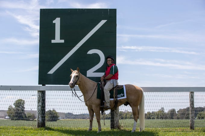 """Outrider Greg Blasi and his horse """"Ricky Junior"""" finds shade from the intense sun in front of the 1/2 mile marker between races at Kentucky Downs. Aug. 31, 2019"""