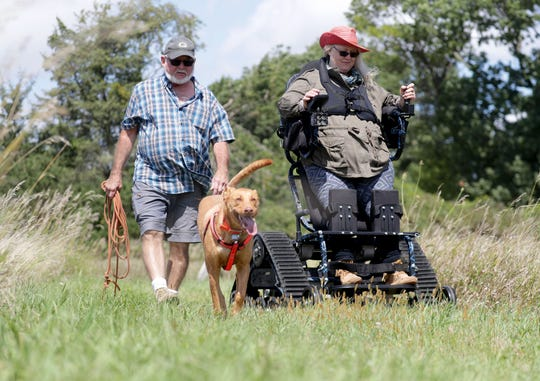 Monica Spaeni and her husband, Steve, hike in a marsh area with their 3-year-old dog, Ragnar, near their home in McFarland on Aug. 28. Monica Spaeni, president of Access Ability Wisconsin, has a fleet of all-terrain wheelchairs available to borrow for free or a donation around the state.