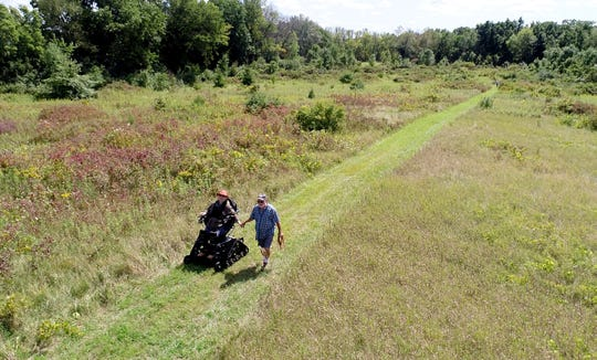 Monica Spaeni and her husband Steve hike in a marsh area with their three-year-old dog, Ragnar, near their home in McFarland on Wednesday, Aug. 28, 2019. Spaeni, president of Access Ability Wisconsin, has a fleet of all-terrain wheelchairs available to borrow for free or a donation around the state.