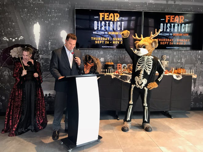 Michael Belot, second from left, announces the Deer District will transform into the Fear District complete with haunted houses, Halloween movie screenings, and themed food and drink. He is joined by scare actors and the Bucks' mascot Bango during a press event on September 3, 2019.
