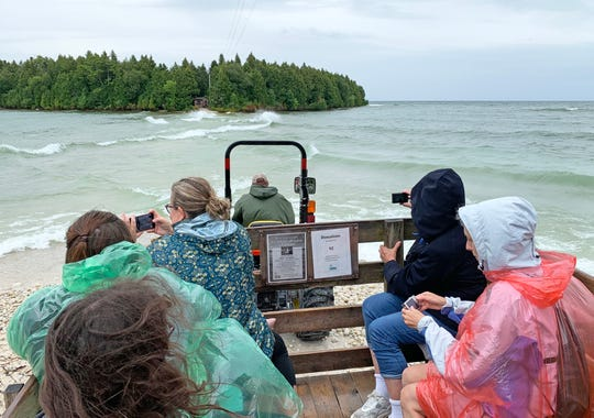 A tractor pulls a wagon of people from the mainland north of Baileys Harbor across a causeway to visit the Cana Island Lighthouse on Lake Michigan in 2019.