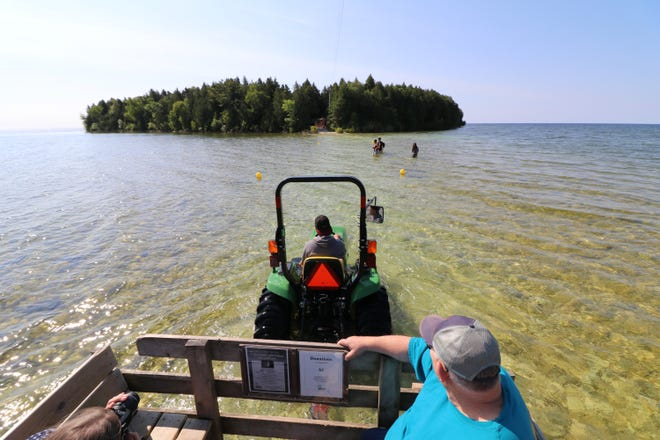 A tractor pulls a wagon full of visitors across a causeway to Cana Island on July 12, 2019.