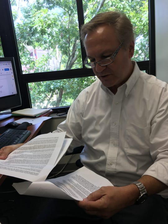 National Freedom of Information Coalition Executive Director Dan Bevarly looks through research at his office on the University of Florida campus.