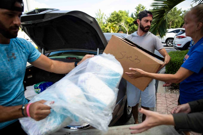 Vinny Sabatino, left, and Jerry Nestico, center, unload over 2,200 diapers donated by Peggy Moberg, president of Naples Wings of Hope, a Collier County charity that was created after Hurricane Irma, at Venue Naples on Tuesday, September 3, 2019. Venue Naples is collecting donations to send to the Bahamas in the wake of Hurricane Dorian, and will be open from 8 a.m. to 4 p.m. through Friday for drop-offs. Volunteers have also offered to pick up donations from residents' homes, and many local businesses have signed up to serve as additional drop-off locations. A full list of needed items and drop-off locations is available on the Venue Naples Facebook page.
