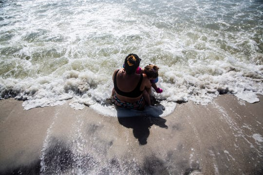Brittant Cyr holds Brielle Jonathan, 3, in her arms as she sits at the shore of Naples Beach on Tuesday, September 3, 2019. Locals and tourists continue visiting scenic spots in Naples, taking advantage of heavy winds and waves bought on by Hurricane Dorian.
